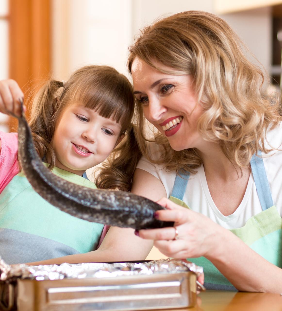 Niña y mujer mirando un pescado